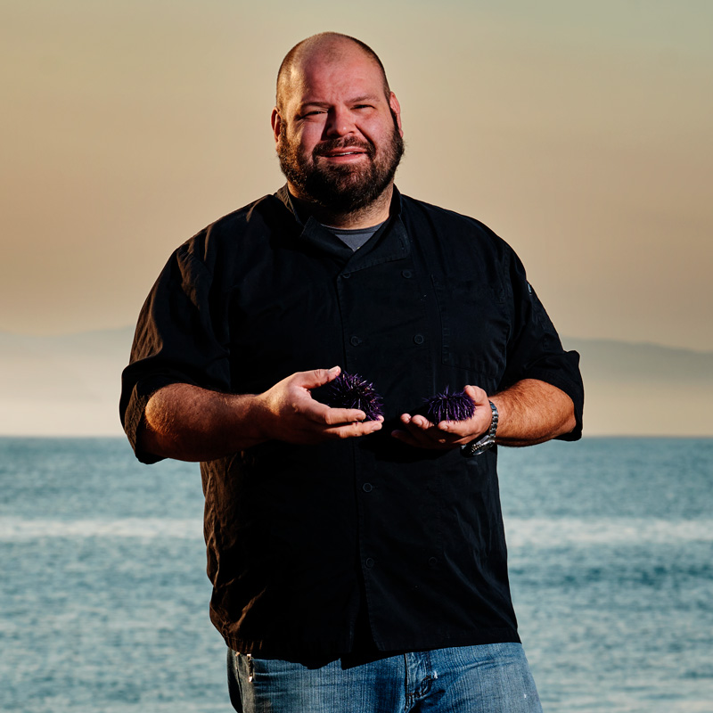 Chef Paul Grossi holding a pile of purple sea urchins on a beach