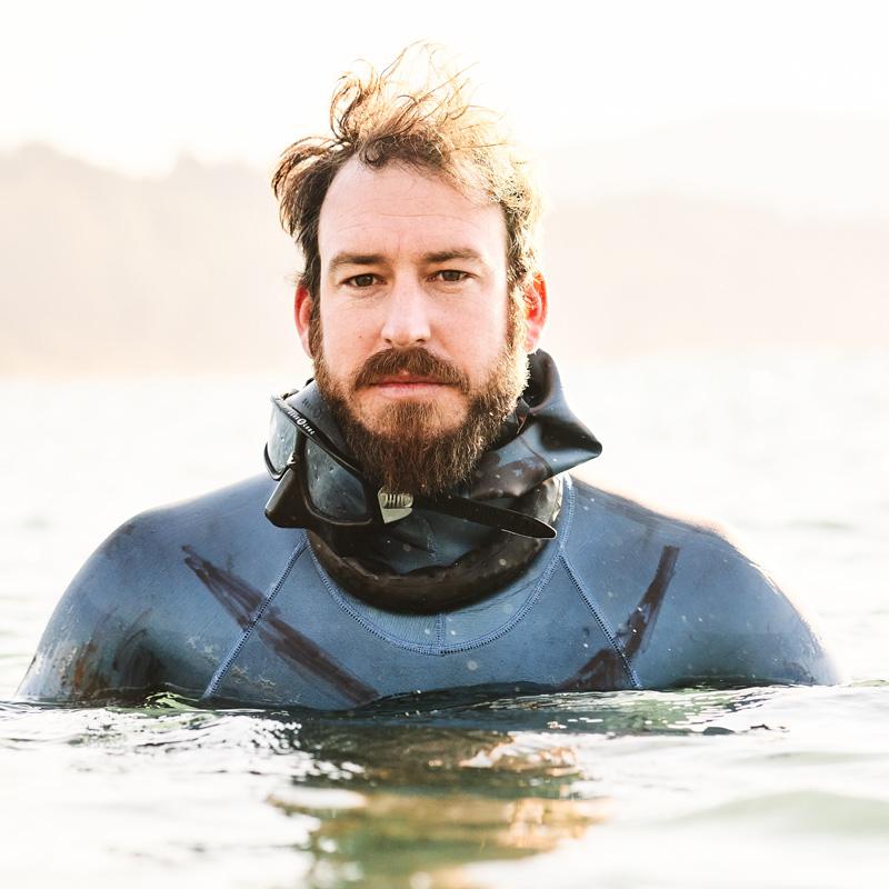 Freediver Grant Hogan chest-deep in water against bright sunlight
